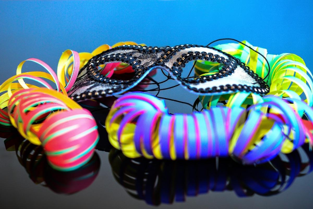 Imagem mostra uma máscara de carnaval em um fundo azul sobre origem do carnaval