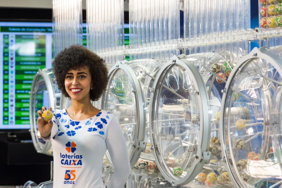 resultado das Loterias Caixa - a imagem mostra uma mulher em primeiro planto segurando uma bola utilizada nos sorteios das Loterias Caixa. Ao fundo, diversos globos que são utilizados nos sorteios dos concursos.
