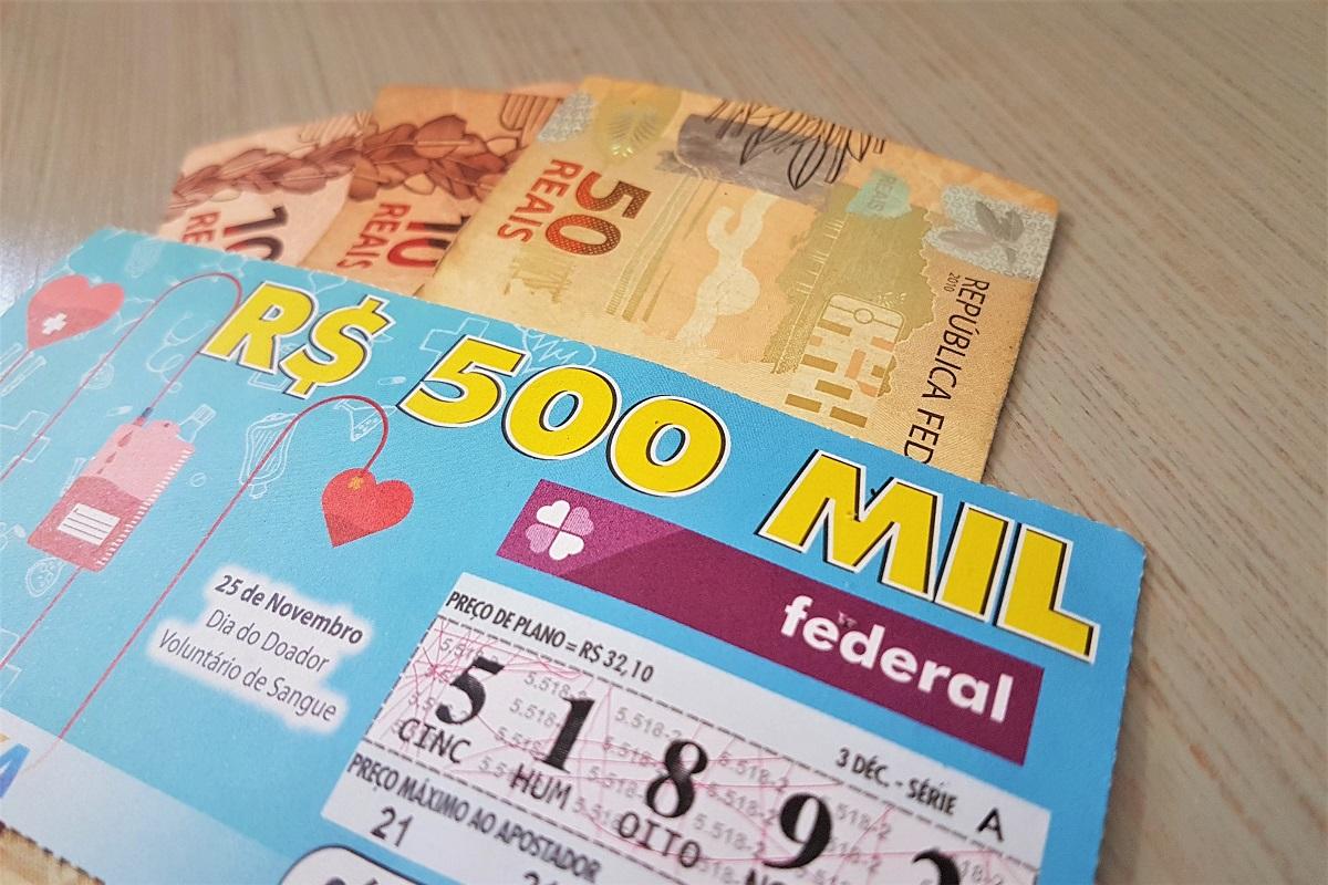 A imagem mostra um bilhete da loteria Federal e notas de dinheiro
