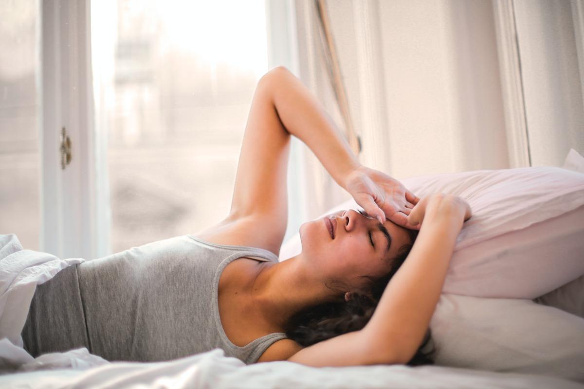 Imagem mostra mulher deitada na cama com dores - o que é a Síndrome de Haff