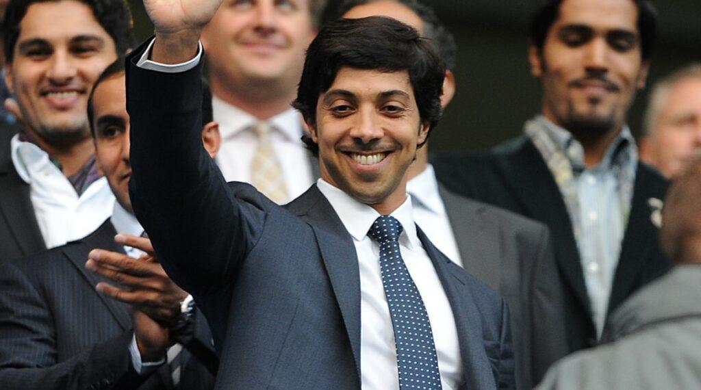 Bin Zayed sorrindo e acenando, usado um terno grafite com uma camisa branca e gravata azul marinho com bolinhas brancas